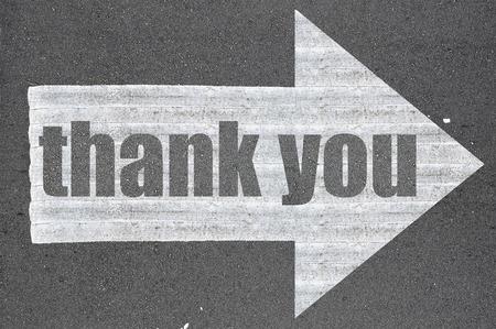 gratitude: Arrow on asphalt road written word thank you  .