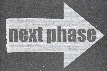 Arrow on asphalt road written word next phase  . Stock Photo