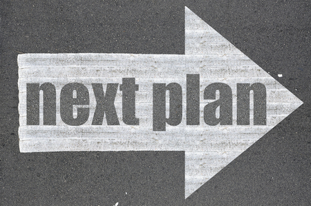 what's ahead: Arrow on asphalt road written word next plan  . Stock Photo