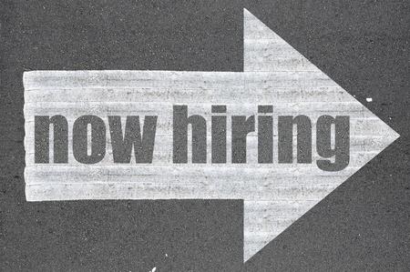 Arrow on asphalt road written word now hiring  . Archivio Fotografico