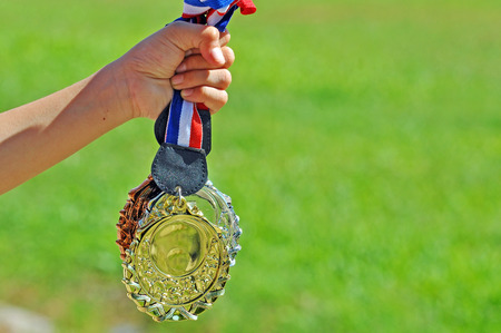 silver medal: Hand hold gold, silver and bronze medal with green field background.