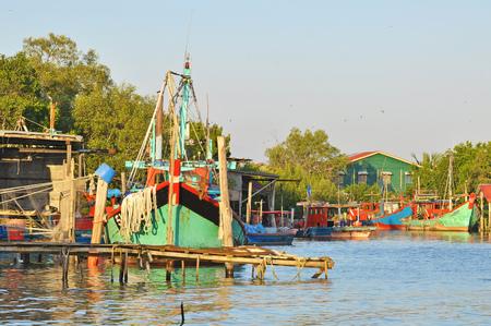 deep sea fishing: wooden jetty and deep sea fishing boat dock at the bay at fishing village. Stock Photo