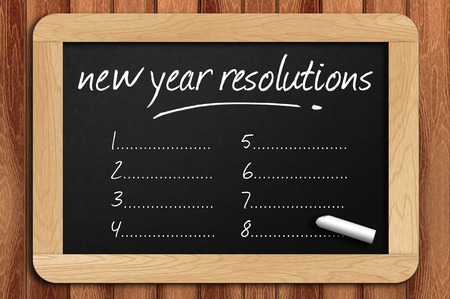 Chalkboard on the wooden table written new year resolutions.