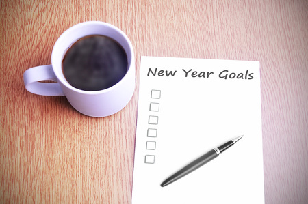 Café en el vector con la nota a escribir nuevas metas del año. Foto de archivo