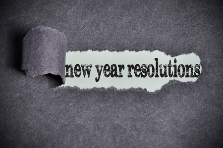 personal decisions: new year resolutions word under torn black sugar paper.