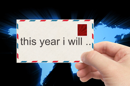 personal decisions: hand holding envelope with this year I will word on world background.