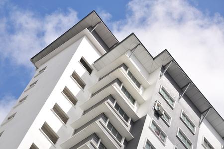Nieuwe hoge luxe appartementencomplex in voorstedelijk gebied met blauwe hemel.