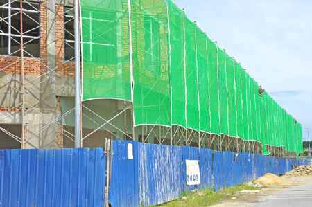 safety net: shop house under construction surround by scaffolding and safety net and fence . Stock Photo