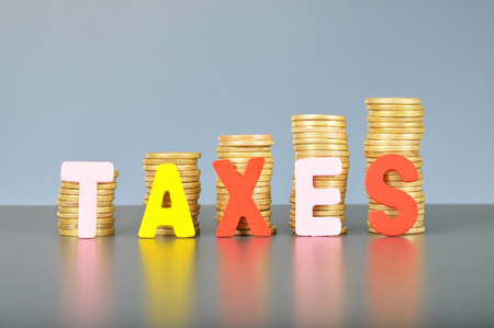 government services: Tax concept with gold stacked coins and alphabet letter. Stock Photo