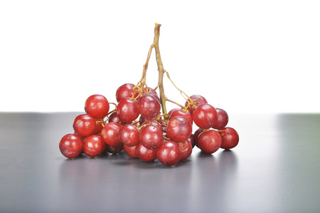 seedless: Delicious bunch red seedless crimson grape on grey and white background. Stock Photo