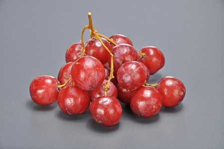 seedless: Delicious bunch red seedless crimson grape on grey background.