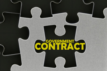 government regulations: The white jigsaw puzzle written word government contract. Stock Photo