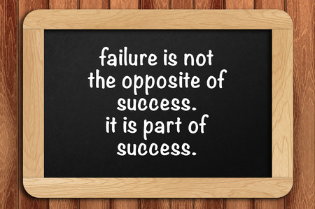 Inspirational motivating quote on chalkboard with wooden background. Failure is not the opposite of success. it is part of success.