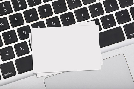 Top view flat lay blank business card on computer keyboard with copy space area