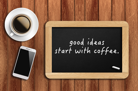 Inspirational motivating quote on chalkboard with coffee, phone and wooden background. good ideas start with coffee. Archivio Fotografico