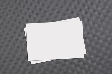 Top view of blank business card on grey paper background.