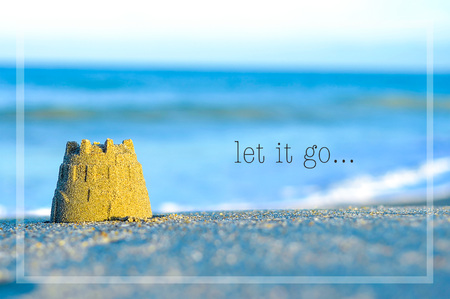 Inspirational motivating quote on blur beach view with sand castle. let it go Archivio Fotografico