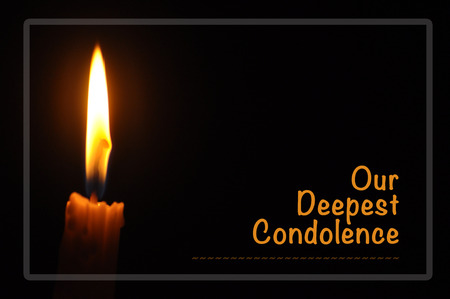 Candle with flame in dark background. Our Deepest Condolences. A sympathetic condolence card design for someone mourning the death of the loved one Archivio Fotografico
