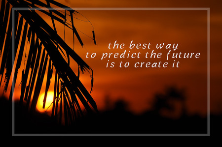 Inspirational motivating quote on silhouette of coconut frond toward sun during sunset. The best way to predict the future is to create it.