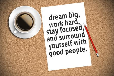 Citation inspirante sur papier avec fond de café, crayon et liège. Rêvez grand, travaillez dur, restez concentré et entourez-vous de bonnes personnes. Banque d'images