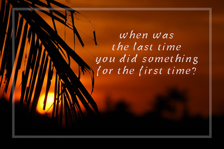 Inspirational motivating quote on silhouette of coconut frond toward sun during sunset. When was the last time you did something for the first time?