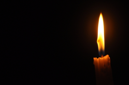 The candle with flame in dark background Archivio Fotografico