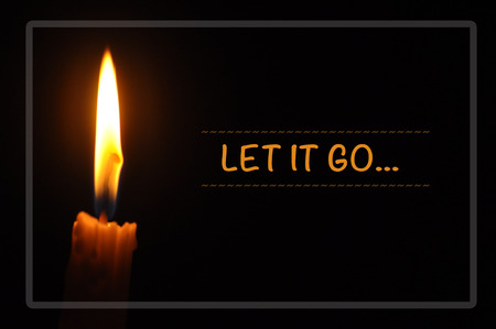 Inspirational motivating quote of candle with flame in dark background. let it go