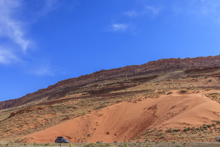 Children slide down the high sandy hill
