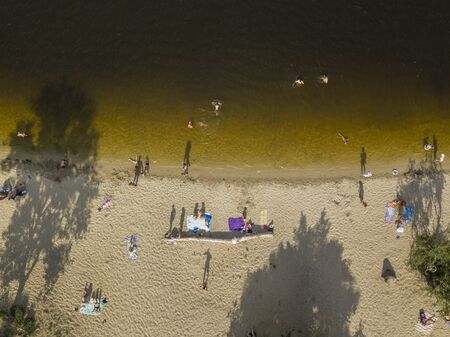 People enjoying the beach and swimming in the sea, aerial view