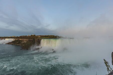 Niagara Falls - American Falls and Bridal Veil Falls with a rainbow in the sunset rays of the setting sun. View from Canadian Side Standard-Bild