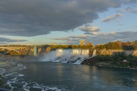 Niagara Falls - American Falls and Bridal Veil Falls with a rainbow in the sunset rays of the setting sun. View from Canadian Side Editorial