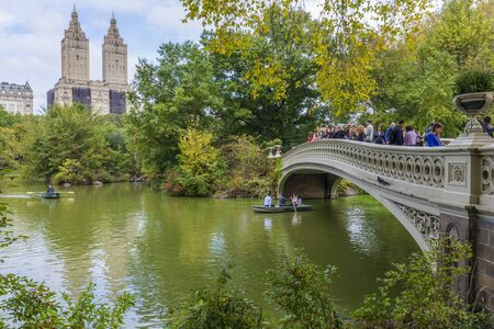 NEW YORK CITY / USA – OCTOBER 12, 2019: Panoramic view of the famous Bow Bridge in Autumn, The San Remo Building, Upper West Side, from Central Park, Manhattan, New York City