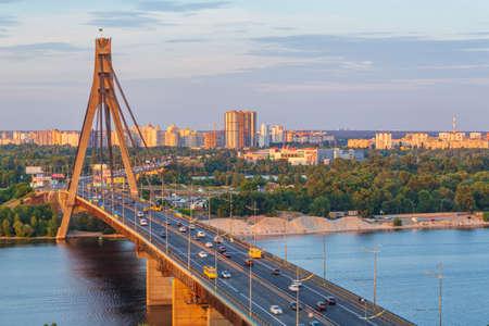 Transport movement on the Moscow bridge at sunset, Kyiv, Ukraine.