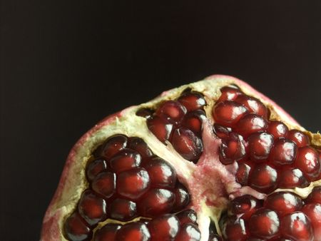 partly peeled pomegranate against a black background photo