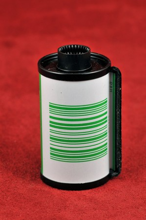 perforation: 35 mm film canister on a red background Stock Photo