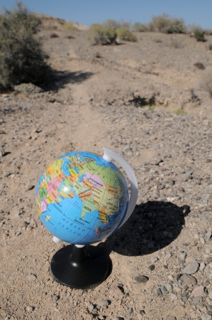 Globe on a road in a mountain desert photo