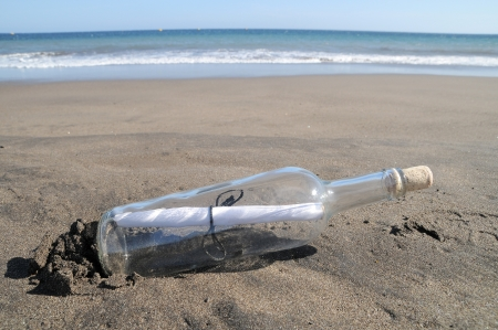 Message in a bottle on a lonely beach ,in Tenerife, Spain photo