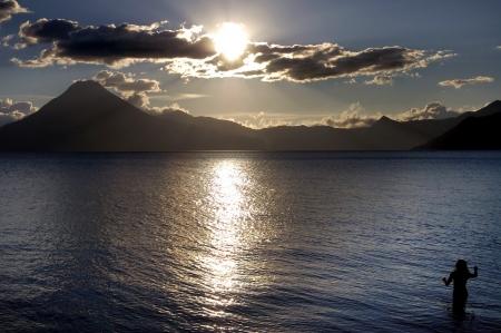 Vulkanische Atitlan Lake in Guatemala met een vrouw bij zonsondergang Stockfoto