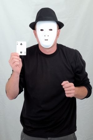 A Masked Mime Holding 2 of Spades on a Gray Background photo