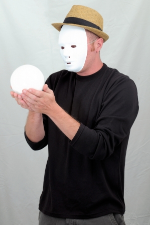 A Masked Mime Holding a White Round Ball photo