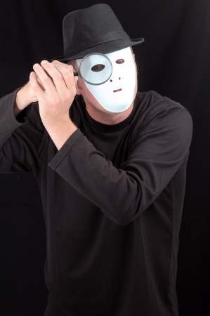 A Masked Mime Holding a Loupe over His Eye photo