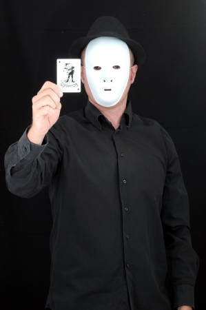 A Masked Mime Holding a Joker Poker Card  photo