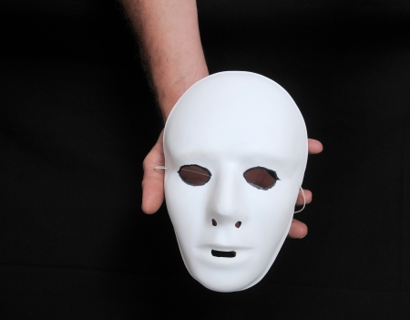 An Hand Holding a Mask over a Black Background photo