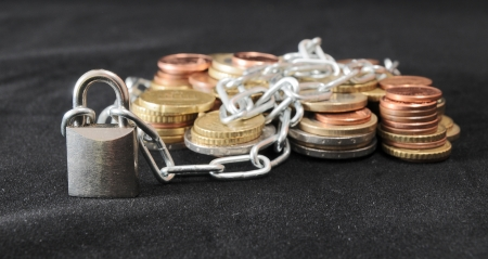 Secure Savings - a Lock and Some Coins on a Black Background photo