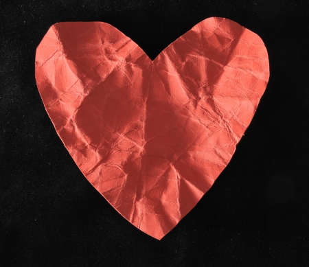 Grunge Red Paper Heart on a Black Background photo