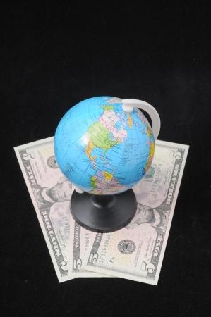 backgruond: Round Globe and Money on a Dark Backgruond