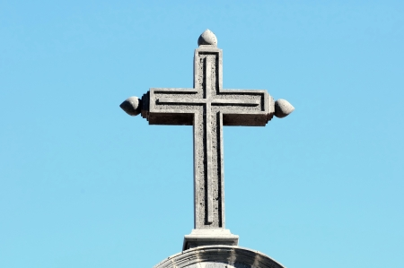 Stone Cross on the Roof of a Church on a Blue Sky photo