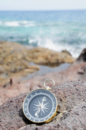 navigational: One Compass on the Rocks near the Atlantic Ocean Stock Photo