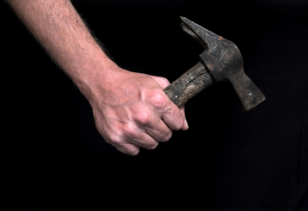 An Hand Holding an Old Hammer over a Black Background photo