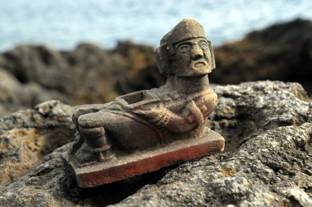 Ancient Maya Statue on the Rocks near the Ocean photo